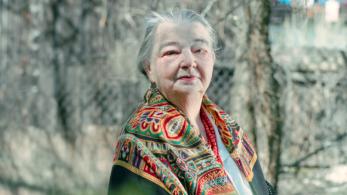 starsza kobieta w stroju regionalnym stoi wśród drzew z których opadły już liście