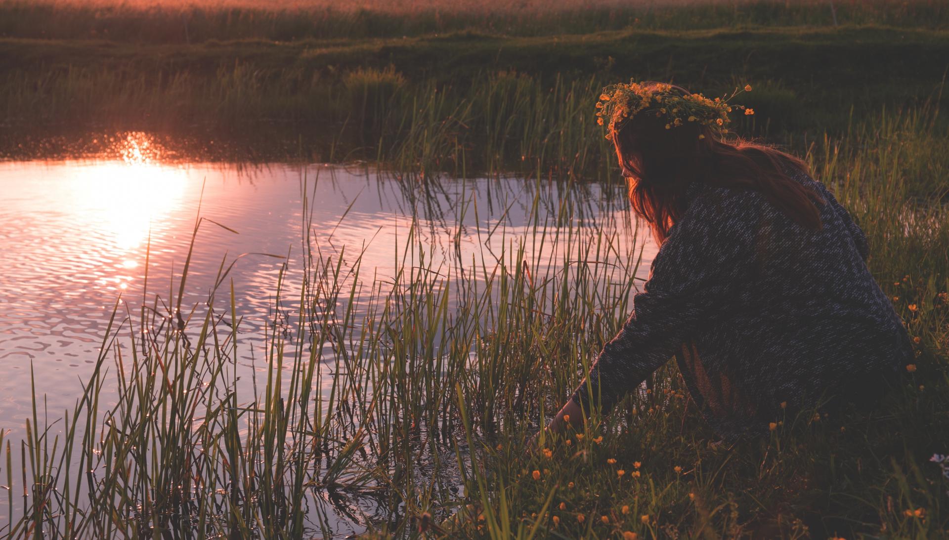 kobieta z wiankiem na głowie kuca przy jeziorze